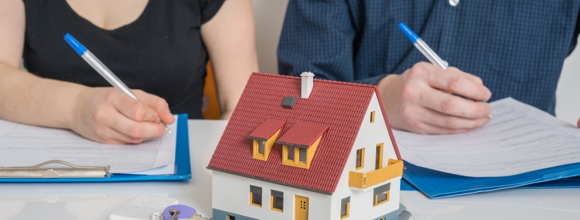 man and woman with pen and paper, model house and keys in front of them representing division of property