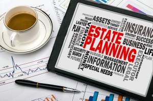 An Estate Planning word graphic, a cup of coffee, and a pen on top of charts and graphs